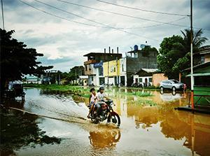 Two people on a motorcycle in a flooded street